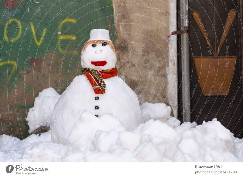 Schneemann mit Schal und Hut steht allein in der Gasse Gesicht gefroren Eis Winter Freizeit Schneemann machen spielerisch weiß Winterzeit Verschlussdeckel