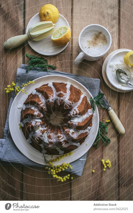 Stilvoll servierter Zitronen-Kokos-Kuchen Dessert Kokosnuss Tisch Teller hölzern Bestandteil dienen dekorieren Veganer Lebensmittel lecker geschmackvoll süß