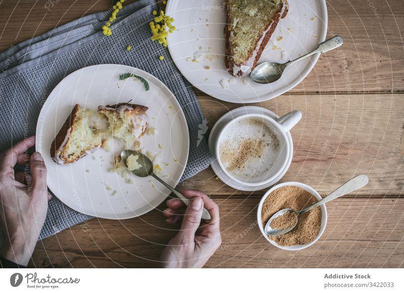Anonyme Frau frühstückt mit köstlichem frischen Kuchen Dessert Zitrone Kokosnuss Scheibe Spielfigur Tasse Kaffee Tisch Teller Hand Arme hölzern Bestandteil