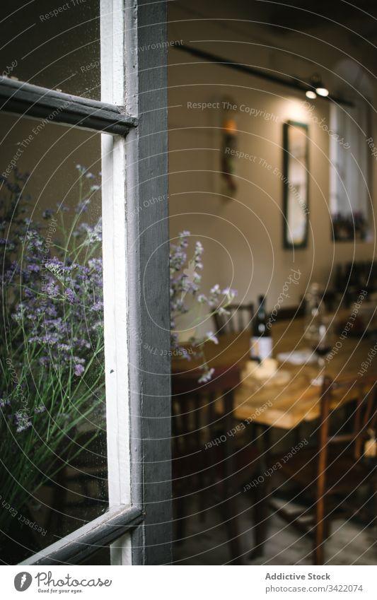 Rustikales Restaurant mit Holztisch und Blumen Café Fenster Tisch Wein rustikal hölzern ländlich Innenbereich Design altehrwürdig gemütlich Dekor retro