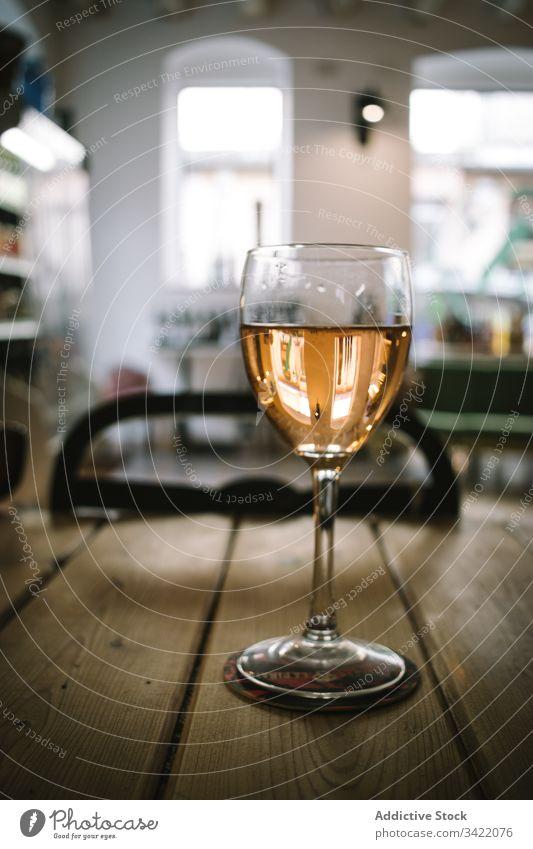 Glas Wein auf Holztisch Tisch hölzern rustikal Weinglas trinken Alkohol Bar Restaurant Getränk liquide Pub durchsichtig Tradition Glaswaren golden