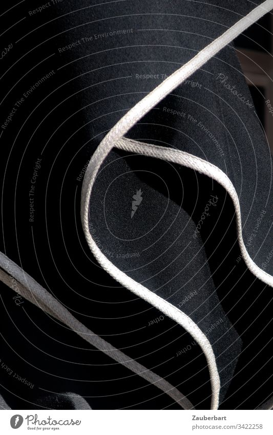 Schwarzer Sonnenschirm mit weißen Streifen, gefaltet, in Nahaufnahme schwarz Falten Strukturen & Formen Linie abstrakt Menschenleer