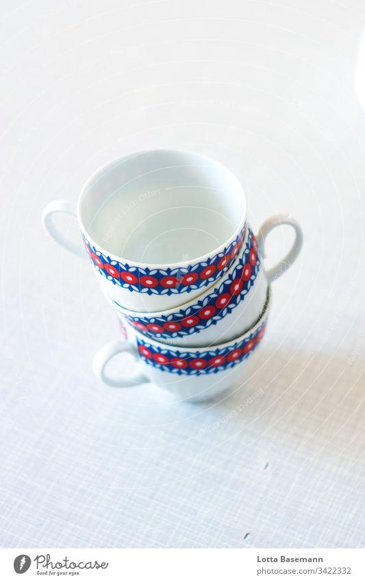 Tassen Stapel Service Kaffeeklatsch retro rot blau weiß Teetasse Kaffeetasse drei Tisch Gedeck Detailaufnahme Nahaufnahme Schwache Tiefenschärfe Muster Geschirr