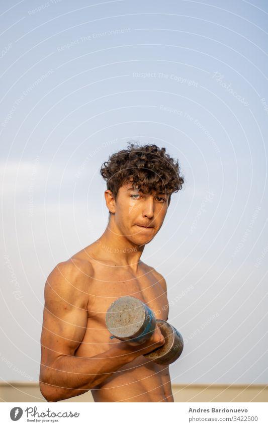 Junger Junge macht bei Sonnenuntergang Fitness ohne Hemd gutaussehend Aerobic posierend Stock attraktiv stark Erwachsener jung Bauchmuskeln Vitalität Muskel