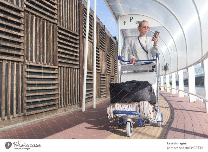 Junge Gelegenheitsfrau benutzt Handy-Anwendung beim Transport von Gepäck vom Ankunftsparkplatz zum Abflugtermin des internationalen Flughafens mit dem Gepäckwagen