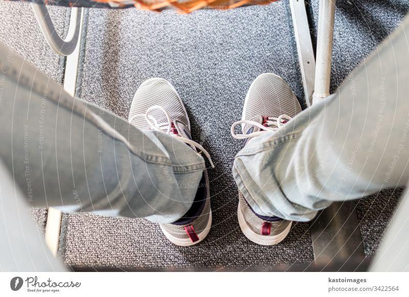 Männlicher Passagier mit Beinfreiheit auf langen Verkehrsflugzeugen. Fokus auf sportliche Turnschuhe Flugzeug Raum Sitz Reise Beine Ebene Transport reisen