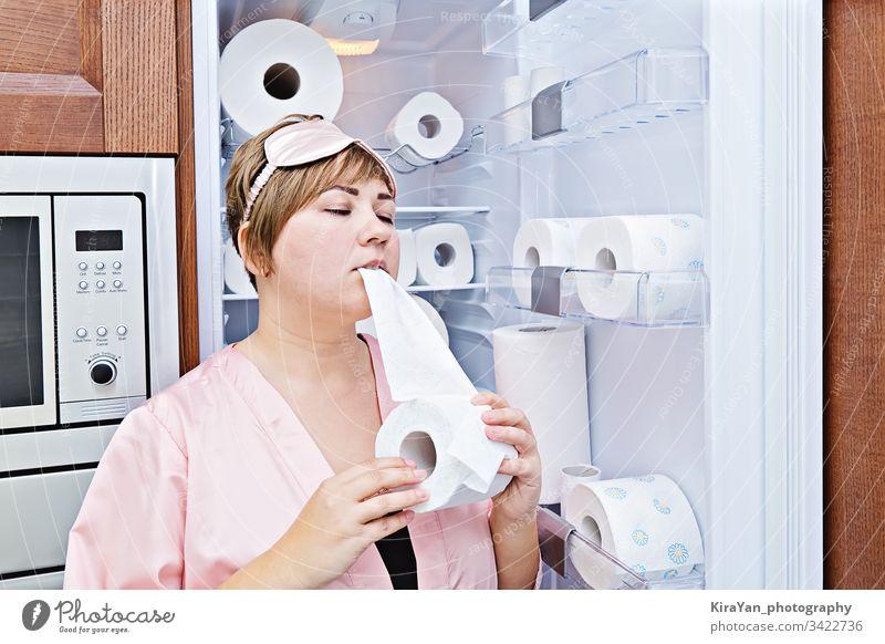 Frau im Schlafanzug isst gierig Toilettenpapier in der Nähe des Kühlschranks, das mit WC-Papier gefüllt ist Nacht Verlangen Coronavirus covid-19 Haushalt