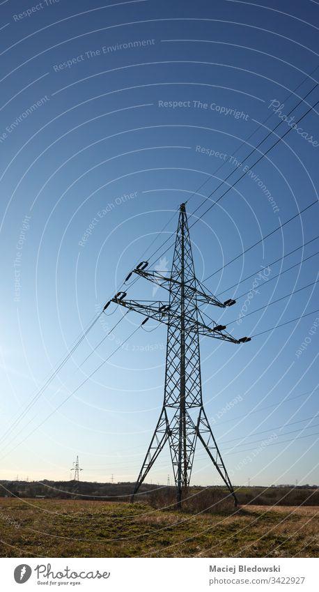 Hochspannungs-Übertragungsmast auf einem Feld gegen die Sonne. Sendemast Industrie Himmel Kraftwerksturm Strommast Energie Kabel Turm elektrisch Elektrizität