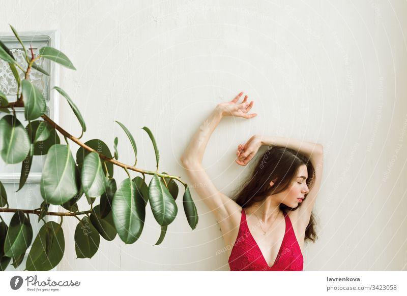 Junge Frau in roter Brünette mit den Händen an der weißen Wand, selektiver Fokus dünn schlank sexy Erwachsener Kaukasier Lifestyle Mädchen schön allein bralette