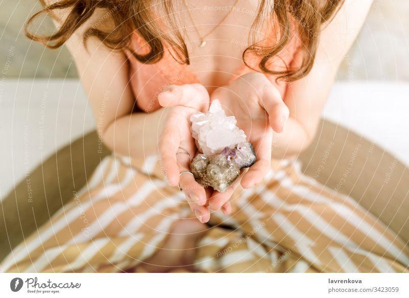Nahaufnahme der Hände einer Frau, die Kristallsteine in den Händen hält, flacher selektiver Fokus ganzheitlich Zauberei u. Magie Steine Energie gemütlich