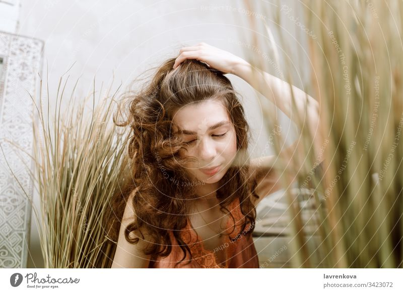 Junge brünette Frau, die den Kopf schüttelt und sich die Haare leckt, selektiver Fokus lockig lässig Kopfschütteln Gras Licht heiter Kaukasier Lifestyle