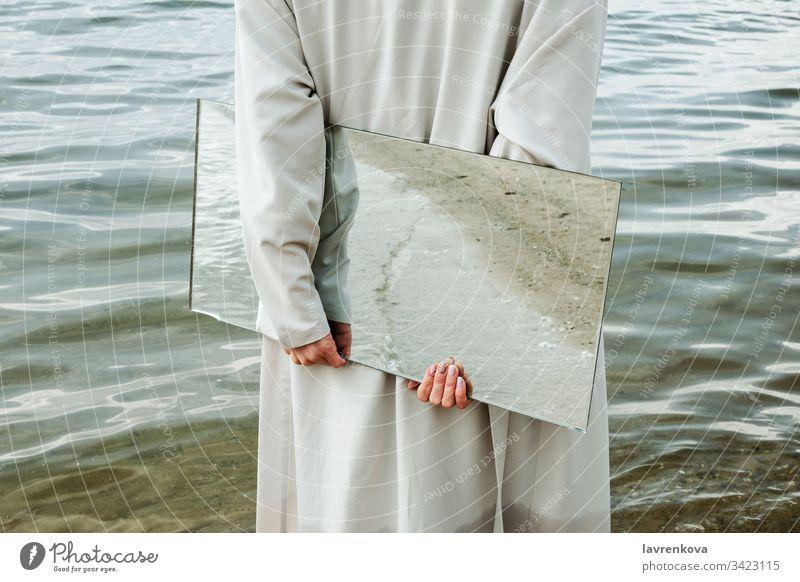 Nahaufnahme einer Frau in blauem Kleid, die am Ufer steht und einen Spiegel hält, in dem sich der Strand spiegelt, selektiv Erwachsener Kaukasier Sauberkeit