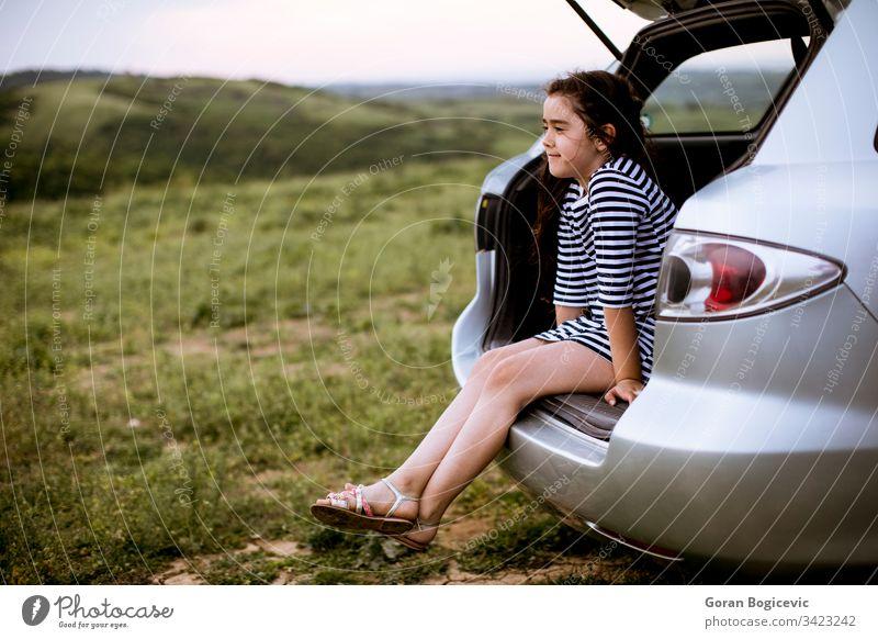 Kleines Mädchen sitzt im offenen Kofferraum des Autos Ausflug PKW reisen Kind Glück Reise Sitzen Tourist Urlaub Fröhlichkeit Natur Kinderbetreuung genießend