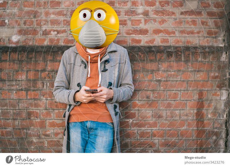 Emoji-Kopf mit Gesichtsschutzmaske. Business Aufruf lässig Zelle Funktelefon Großstadt Mitteilung Gerät Emojis Glück Internet Lifestyle Blick Nachricht Mobile