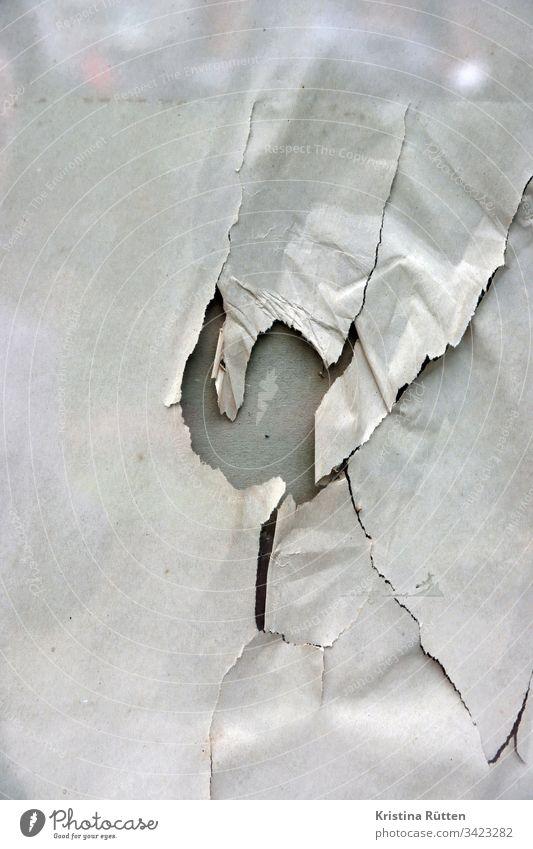 papier mit loch hinter glasscheibe packpapier gerissen kaputt fenster schaufenster spiegelung struktur textur hintergrund material oberfläche zerstört abstrakt