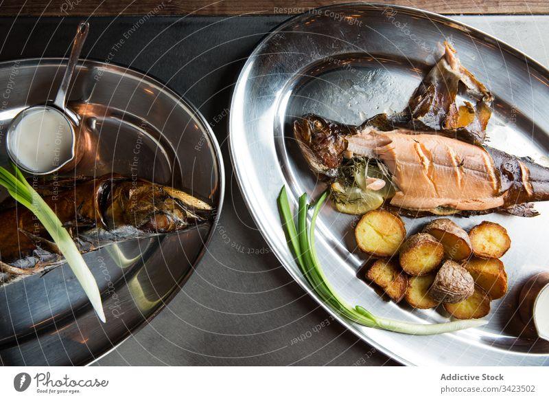 Gebratener Fisch und Kartoffeln mit Sahnesoße und frischer Schalotte Grillrost Restaurant Teller Frühlingszwiebel Saucen Lebensmittel Mahlzeit lecker