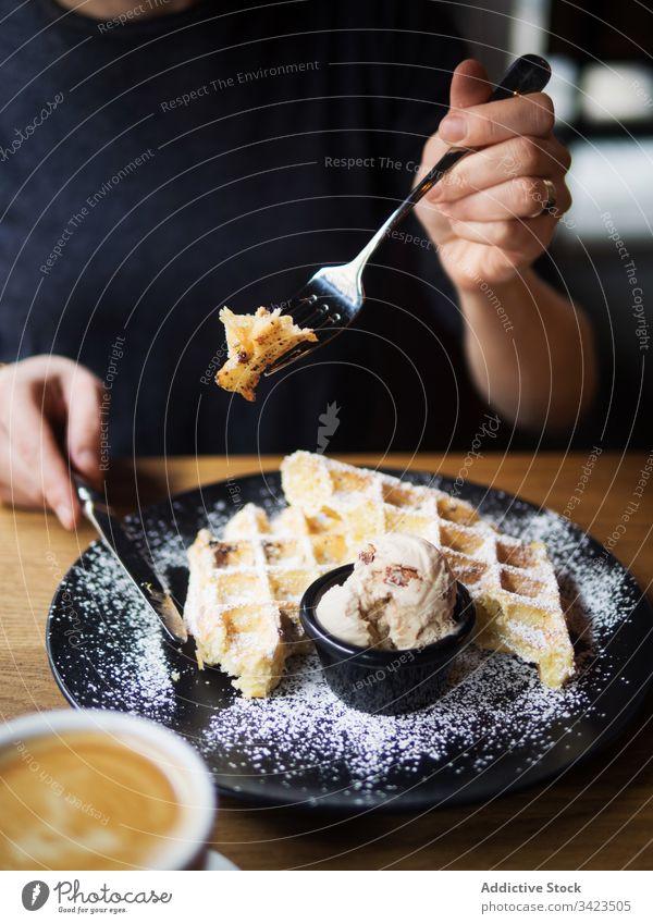 Anonyme Person, die in der Nähe von Kaffee Waffeln mit Eis isst Speiseeis Café essen geschnitten süß Tisch sitzen Gabel Messer lecker Lebensmittel geschmackvoll