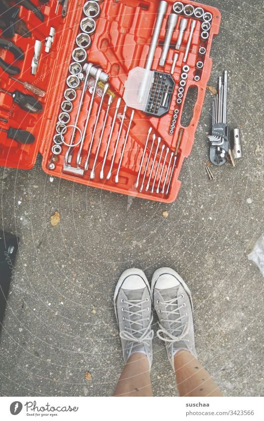 frau steht vor werkzeugskoffer Werkzeug Werkzeugskoffer Heimwerker Handwerker Heimwerkerin Beine Füße Frau Schuhe Turnschuhe Schraubenschlüssel Schraubenzieher