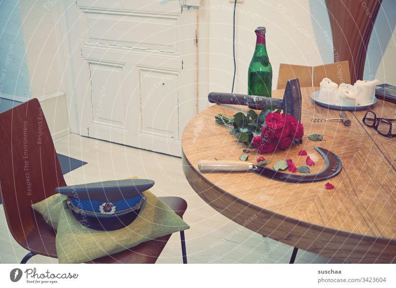 hammer und sichel liegen auf einem tisch, nebst geleerter weinflasche, einem strauß roter rosen und einer militärmütze Fotochallenge Hammer Sichel Tisch Küche