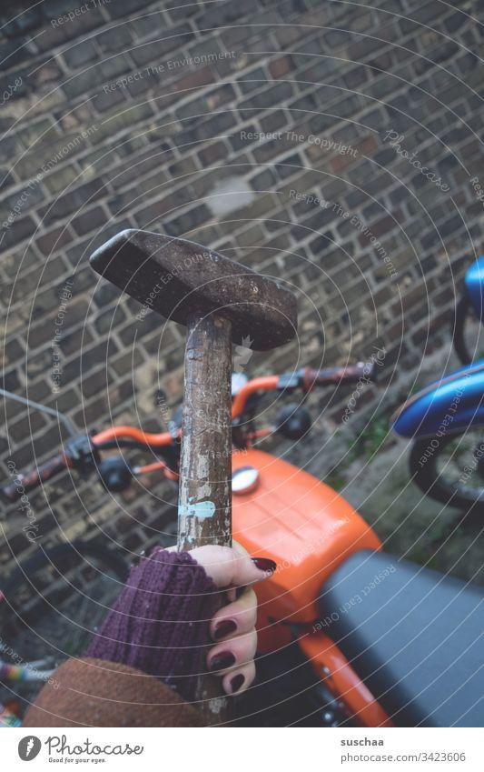 frau hält einen hammer über ein orangefarbenes moped vor mauerwerk Frau weiblich Hand Finger Hammer Werkzeug Moped lackierte Fingernägel Motorrad Lenker Rad