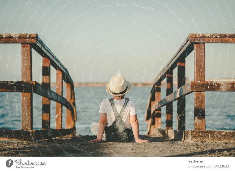 Rückenansicht eines nachdenklichen Kindes, das auf das Meer schaut Kindheit nostalgisch Gedanke Einsamkeit einsam Ausdruck Freiheit Unschuld Porträt ernst