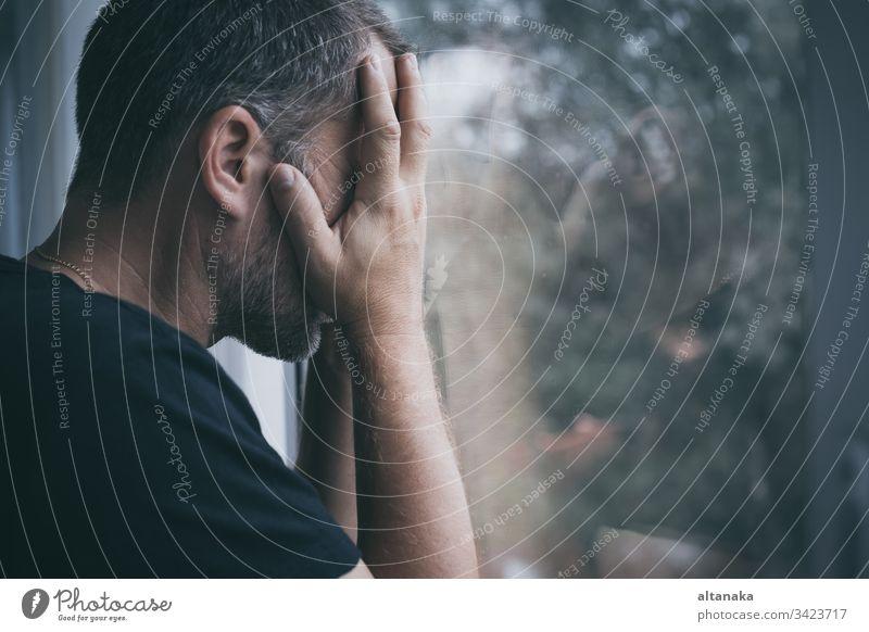 Porträt eines traurigen Mannes, der in der Nähe eines Fensters steht Traurigkeit Verlust Problematik deprimiert ernst Angst Trauer Frustration unglücklich