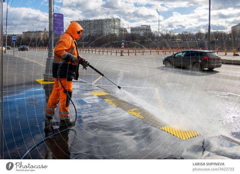 Straßenarbeiter reinigen Stadtstraße mit Hochdruckreiniger, Reinigung verschmutzter Haltestellen des öffentlichen Verkehrs, Moskau, Russland industriell