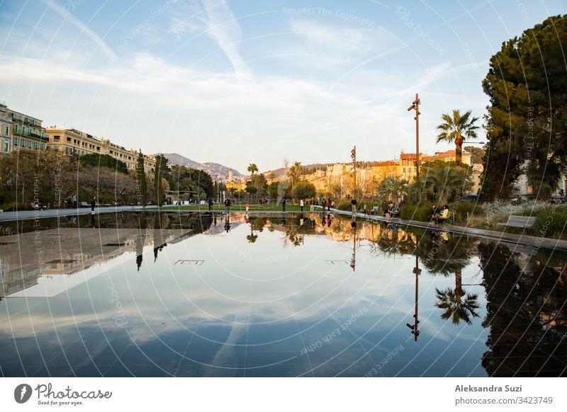 Nizza, Frankreich - 20.03.2018: Springbrunnen auf der Promenade du Paillon, Spiegelungen auf der Wasseroberfläche, Sonnenuntergang. Alpen Architektur Gegend