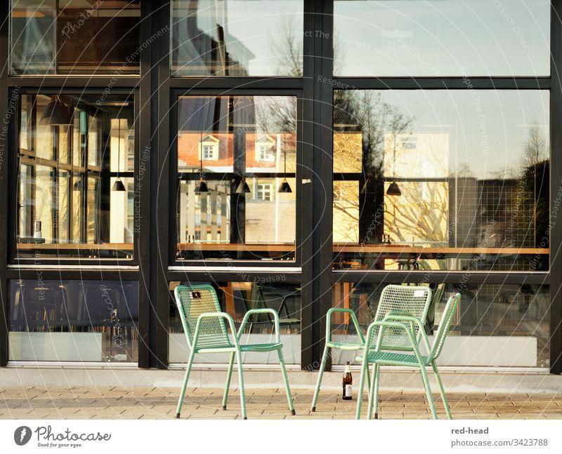 menschenleere Stühle auf öffentlichem Platz vor leerer Kantine - mit einer einzelnen stehengelassenen Bierflasche - Stuhlgruppe Glasfassade trist Stahl Farbfoto