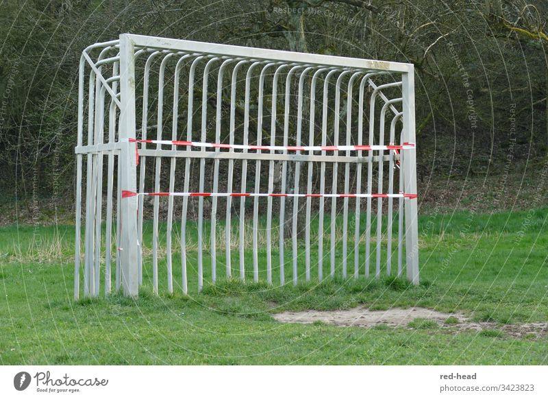Metallfussballtor auf dem Fussballfeld, das wegen Corona mit einem Flatterband geschlossen wurde Fußballtor gesperrt grün Spielplatz Fußballfeld Tor im Freien