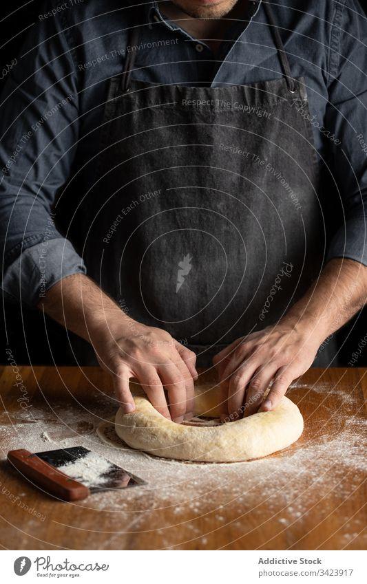 Bäcker formt Brot in der Küche Teigwaren vorbereiten Lebensmittel Koch Küchenchef rund Mann Golfloch Gebäck Formular Tisch kulinarisch selbstgemacht