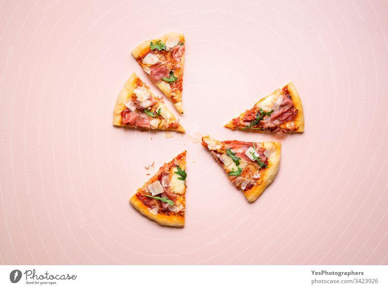 Pizzaschinkenscheiben auf rosa Hintergrund. Italienisches Volksgericht Rucola Kohlenhydrate Käse und Schinken Küche Abendessen Essen Europäer berühmt Fastfood
