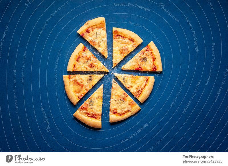 Pizzascheiben auf blauem Hintergrund. 4 Käse-Pizzascheiben 4-Käse-Pizza Italienisch obere Ansicht Kohlenhydrate klassisches Blau Kruste Küche Abendessen