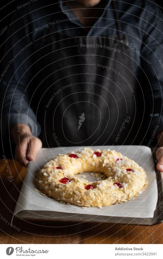 Bäcker bereitet Brot am Holztisch zu Lebensmittel vorbereiten Koch Küchenchef Teigwaren rund ungekocht Mann Bäckerei Gebäck Tisch hölzern Mahlzeit kulinarisch