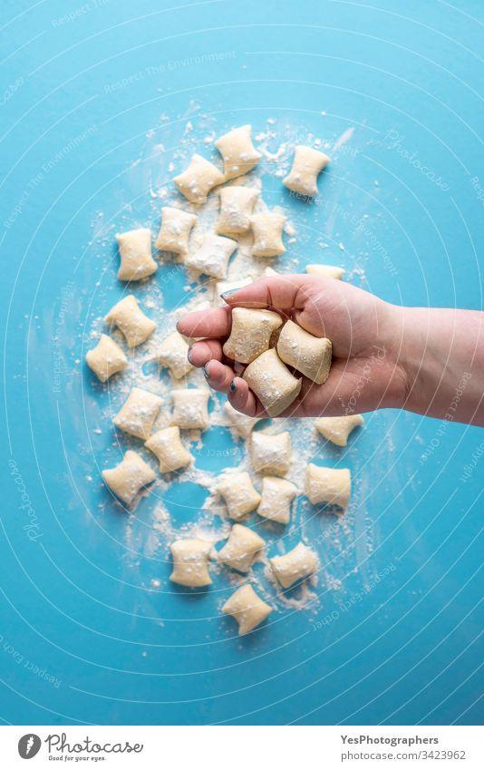 Gnocchi-Knödel ungekocht. Käse-Gnocchi in der Hand Italienisch obere Ansicht blau Essen zubereiten Küche Diät Abendessen Europäer flache Verlegung Mehl