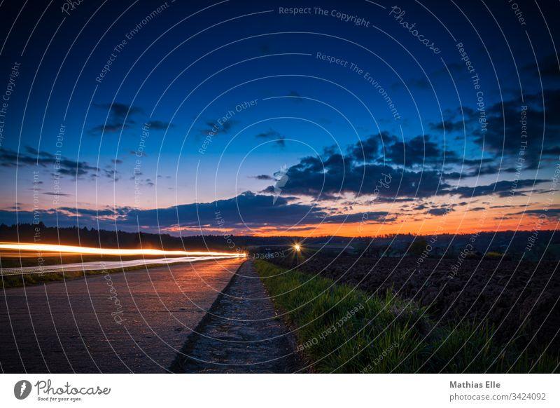 Leuchtspuren vom Auto auf einer Landstraße Langzeitbelichtung Lichterscheinung Außenaufnahme Textfreiraum oben mehrfarbig Nacht dunkel Farbfoto Nachtleben