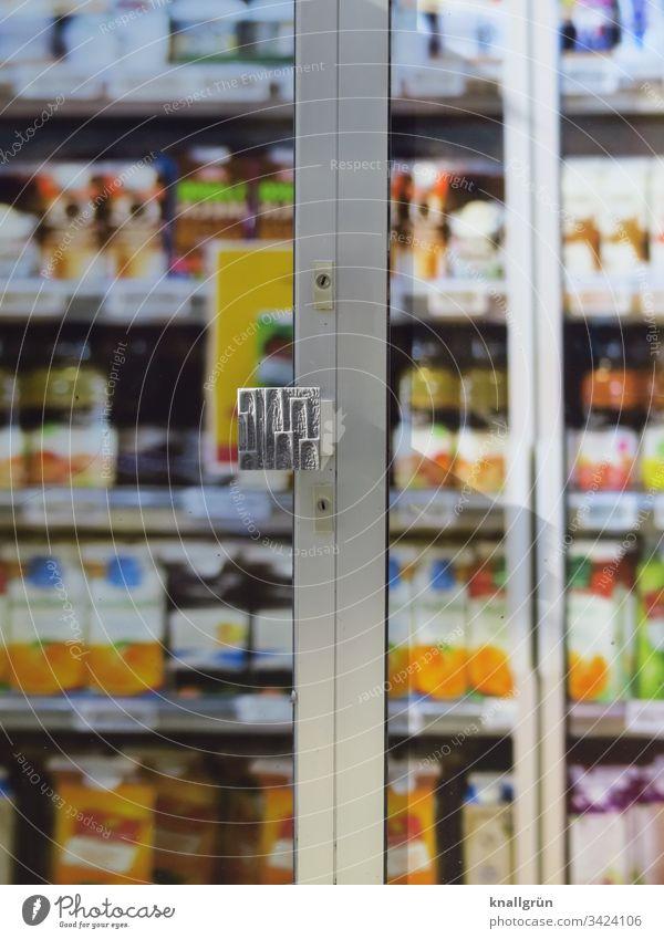 Blick durch die geschlossene Eingangstür eines Supermarktes auf volle Lebensmittelregale Lebensmittelgeschäft Discounter Farbfoto Tür Außenaufnahme Menschenleer