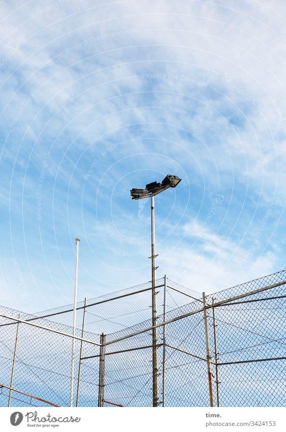 Geschichten vom Zaun (77) zaun himmel grenze wolken schutz sicherheit blau hoch frisch dicht geschlossen absperrung wind wehen flutlicht flutlichtanlage
