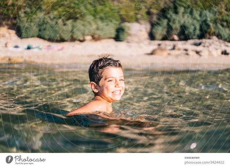 Lustiges Kind schwimmt auf dem Meer Aktivität Baby Strand schön Schönheit blau Junge hell Kaukasier heiter Kindheit Küste Kultur niedlich Genuss Gesicht Familie