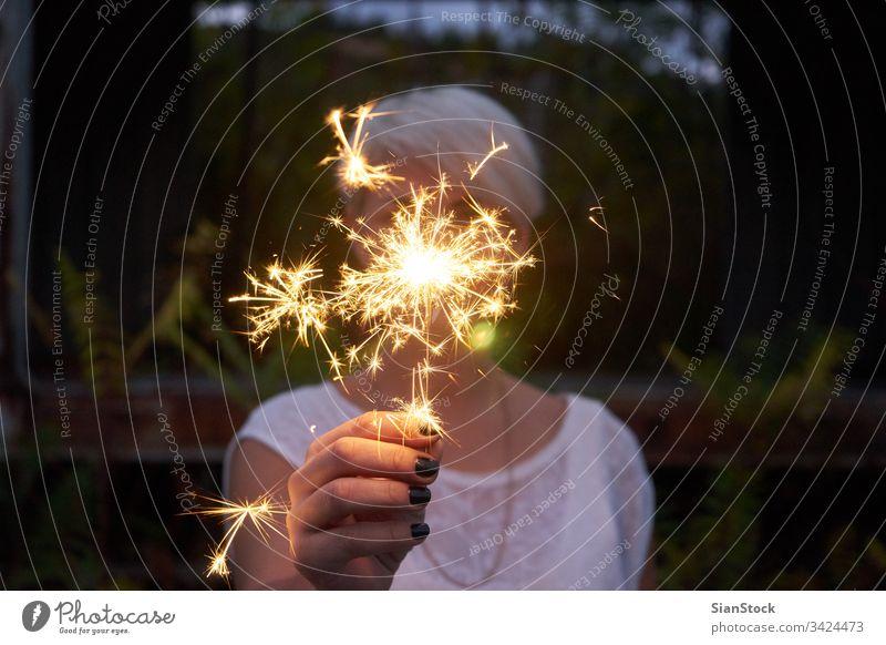 Blonde Frau amüsiert sich mit einer Wunderkerze. glühend Person Flamme Party Wald Winter Wälder See funkeln Jahr jung Feiertag schön Beteiligung Vorabend Funken
