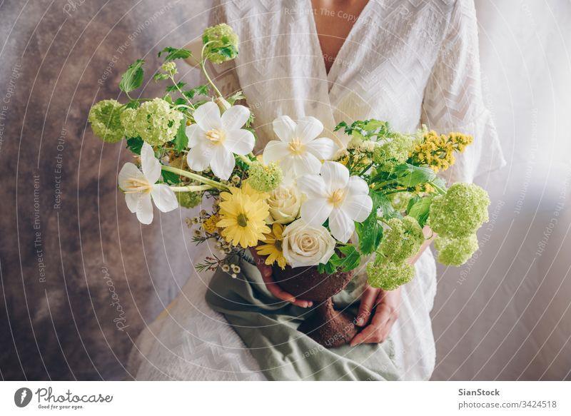 Junge Frau in einem weißen Kleid, die eine Vase mit Blumen hält. Vintage, romantisches Konzept. Blumenstrauß Mädchen Metall sitzen Sitzen Stuhl weiches Licht