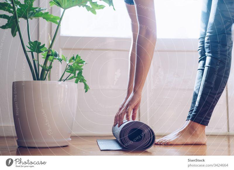 Nahaufnahme einer jungen Frau, die ihre Yogamatte faltet Unterlage Fitness schön Sport Gesundheit Übung passen Training Wellness Fitnessstudio Mädchen Pilates