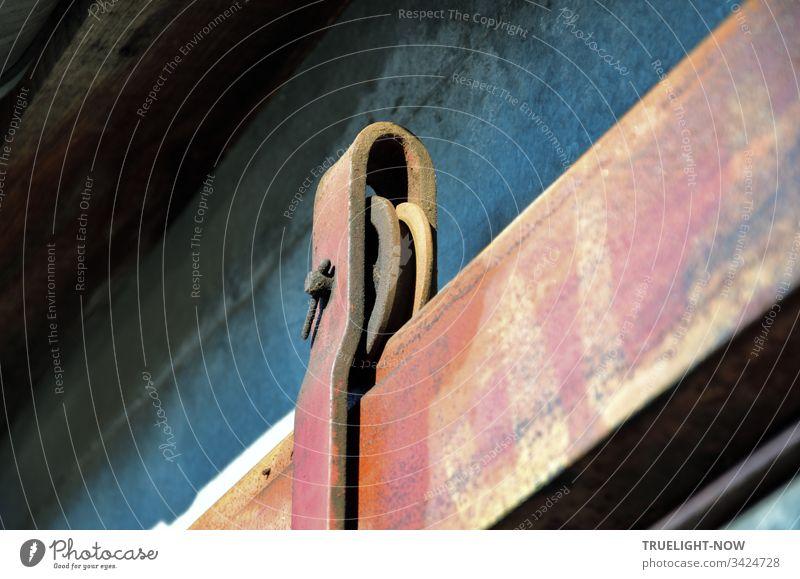 Detail einer alten, schweren Eisenkonstruktion in U-Form, die ein Eisenrad hält, welches in einer Achse auf einer Schiene rollt und so die Bewegung eines daran aufgehängten Schiebetores in der Horizontalen ermöglicht.