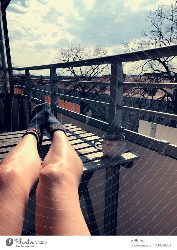 Sich Sonnen auf dem Balkon beim Home Office Sonnenschein Kaffee Tasse Beine Tisch bräunen faulenzen ausruhen Pause bequem genießen nackte Beine Socken