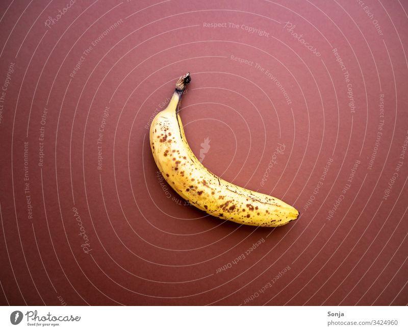 Überreife Banane mit Punkten auf einem braunen Hintergrund überreif punkte hintergrund draufsicht noch gut wegwerfen Lebensmittel Detailaufnahme Bioprodukte