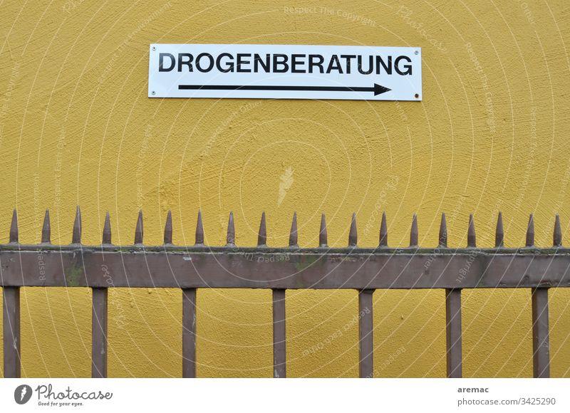 Schild Drogenberatung an einer gelben Wand Beratung Zaun Metall Spitzen Außenaufnahme Hinweisschild Schilder & Markierungen Mauer Buchstaben weiß