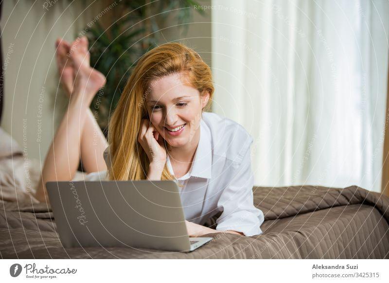 Junge Frau mit langen Haaren, die morgens im Schlafzimmer auf dem Bett liegt, ein Hemd trägt, online chattet, telefoniert, lächelt. Erwachsener schön Schönheit