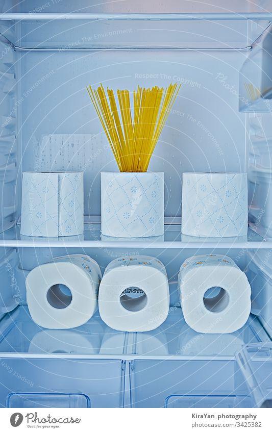 Rollen Toilettenpapier und Spaghetti auf Regalen im Kühlschrank als Symbol der Hysterie Coronavirus covid-19 rollen Papier Küche Haushalt Streich Gewebe