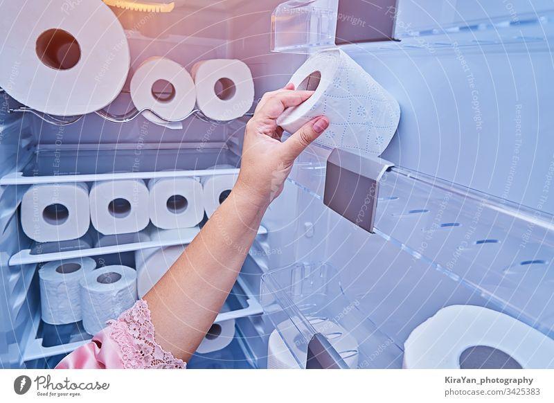 Weibliche Hand nimmt eine Rolle Toilettenpapier von der Kühlschranktür Coronavirus covid-19 Frau nehmen rollen Papier Küche Haushalt Streich Gewebe heimwärts