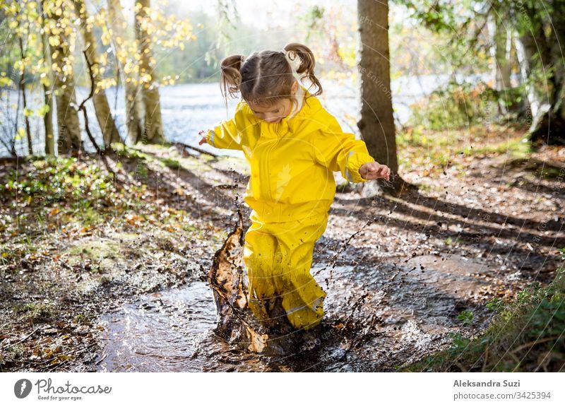 Süßes kleines Mädchen springt in einer schlammigen Pfütze und trägt einen gelben Gummioverall. Glückliche Kindheit. Sonniger Herbstwald bezaubernd Stiefel offen